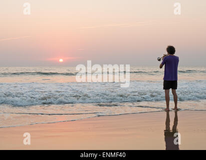 A man playing a trumpet on Agonda beach in Goa South India at sunset - Stock Image