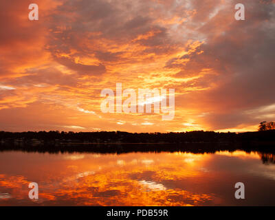 A huge Orange stratocumulus cloudy sunrise seascape, over sea water with water reflections. Queensland, Australia. - Stock Image