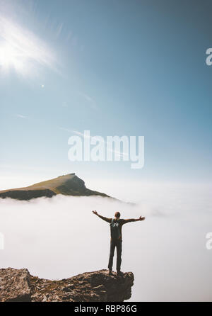 Hiker man standing alone on mountain cliff edge over clouds raised hands adventure travel lifestyle vacations activity outdoor success emotions - Stock Image