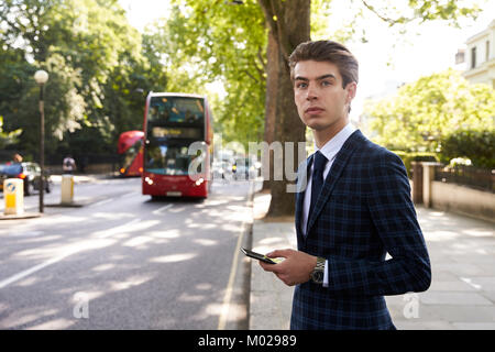 Young businessman standing in the street holding smartphone - Stock Image