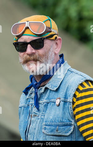 Chichester, West Sussex, UK. 14th Sep, 2013. Goodwood Revival. Goodwood Racing Circuit, West Sussex - Saturday 14th September. Portrait of a biker dressed in a yellow and black striped top and denim vest with dark sunglasses. Credit:  MeonStock/Alamy Live News - Stock Image