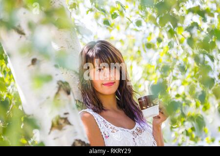 Attractive teenager girl is drinking coffee in nature looking at camera - Stock Image