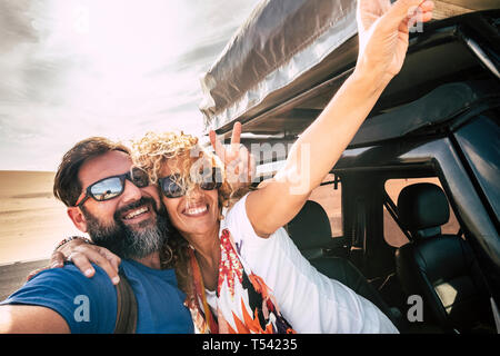 Happy couple cheerful and smile in selfie picture style together hugging with relationship and happiness during car travel - desert and sky in backgor - Stock Image