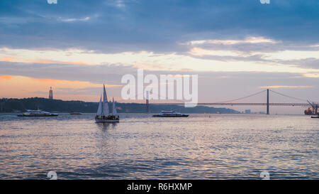 Lisbon, Portugal - Oct 23, 2018: Sunset on River Tagus, Lisbon, Portugal with 25 April Bridge in background and boats - Stock Image