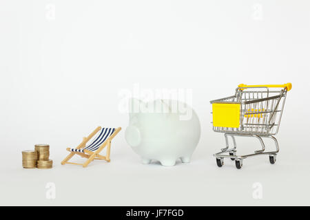 A stack of coins with a deck chair, piggy bank and a shopping cart on white background, copyspace - Stock Image