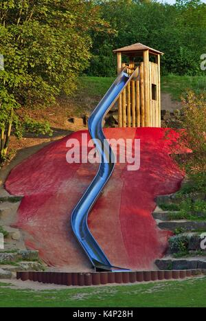 Large metal slide on playground, wooden tower - Stock Image