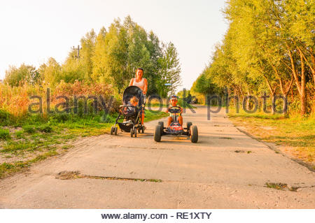 Sarbinowo, Poland - August 9, 2018: Boy sitting in a pedal go kart on a road at the seaside on a warm summer day. Woman with baby buggy following. - Stock Image