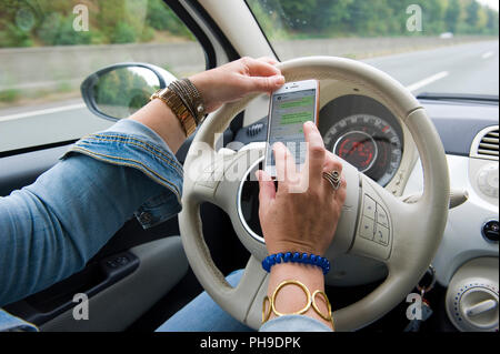 BOTTROP, GERMANY - AUG 16, 2018: A blond woman is whatsapping on her smartphone while she is driving on a highway in full speed. - Stock Image