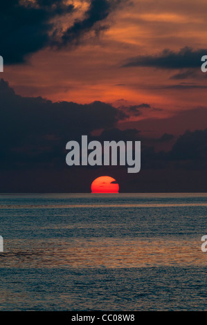 The sun is partly below the horizon, with the calm waters of the Pacific Ocean in the bottom of frame and the orange - Stock Image