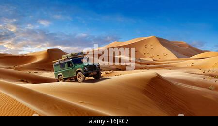 Land Rover Defender amongst the Sahara sand dunes of erg Chebbi, Morocco, Africa - Stock Image