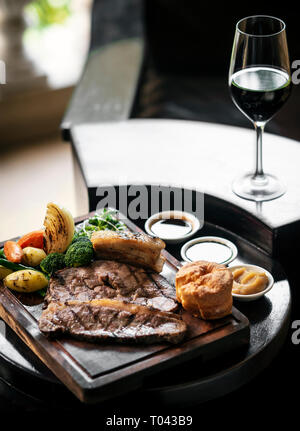 gourmet sunday roast beef traditional british meal set on old wooden pub table - Stock Image