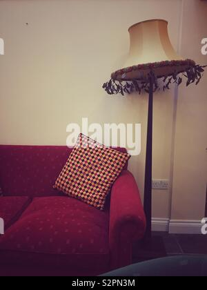 An old fashioned home interior lounge or sitting room with a seventies standard lamp and cozy sofa or armchair - Stock Image
