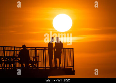 Aberystwyth Wales UK, Wednesday 03 July 2019  UK Weather: People standing at the end of Aberystwyth's truncated  seaside pier are silhouetted against the sky as they watch the glorious sunset  over  Cardigan Bay on the coast of west Wales.   photo credit: Keith Morris/Alamy Live News - Stock Image