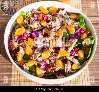 Summer food: mackerel salad meal swith clementines and beetroot served outdoors in white crockery bowl - Stock Image