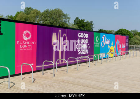 Colourful advertising hoardings showing upcoming new store openings; Rushden Lakes Shopping Centre, Northamptonshire, UK - Stock Image