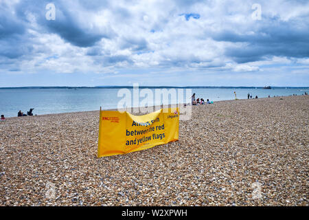Dark clouds over the beach at Southsea with the RNLI sign for lifeguards - Stock Image