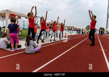 Girls dancing with an instructor on a professional running track on a stadium. - Stock Image
