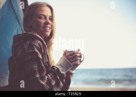 Cheerful beautiful young blonde girl traveler hold a cup of beverage coffee or tea inside her tent camping at the beach with freedom and ocean view -  - Stock Image