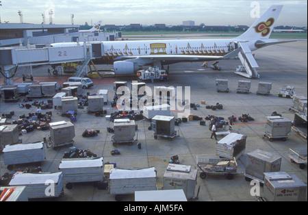 Karachi airport Pakistan unloading the luggage outdoors among the waiting jet planes - Stock Image