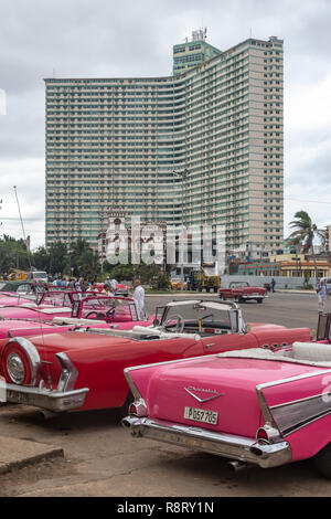 A row of Cuban / American cars in front of the teal-painted, brutalist FOCSA building in Havana. The building from above is shaped like a boomerang. - Stock Image