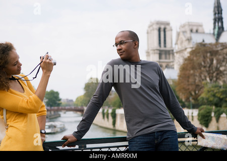 African woman taking photograph of boyfriend - Stock Image