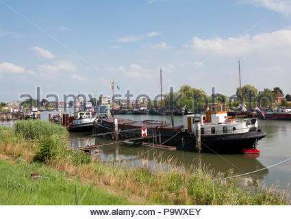 Ouderkerk aan den Ijssel The Netherlands Typical ships berthed along the Hollandsche Ijssel. - Stock Image