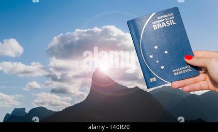 Hand holding Brazilian passport with Christ Redeemer statue in Rio de Janeiro, Brazil in background - digital composite - Stock Image