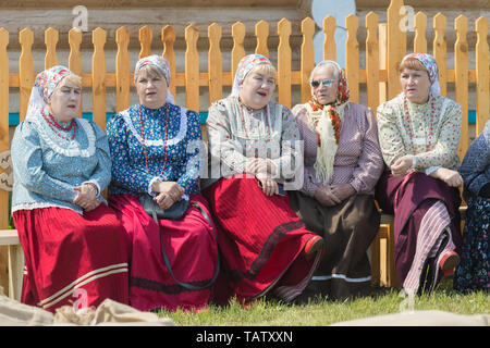 RUSSIA, Nikolskoe village, Republic of Tatarstan 25-05-2019: A group of old women sitting on the bench and talking. Mid shot - Stock Image