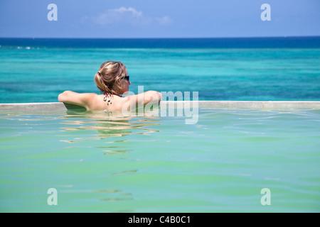Zanzibar, Shooting Star Lodge. A guest relaxes in the infinity pool overlooking Zanzibar's east coast. MR. - Stock Image