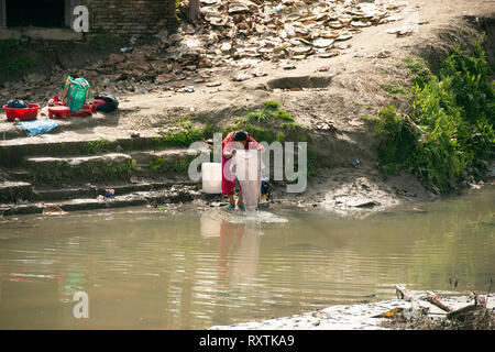 A Nepali lady does her laundry the old-fashioned way in the local river. Bhaktapur, Nepal. - Stock Image