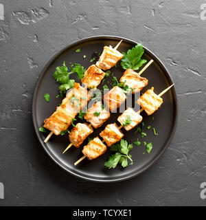 Close up of grilled salmon kebab. Barbecue salmon skewers on black stone background. Top view, flat lay - Stock Image