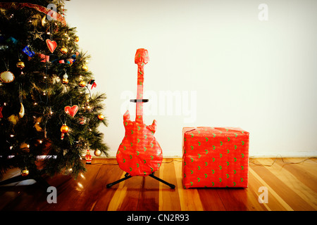 Guitar and amplfier christmas presents with tree. - Stock Image
