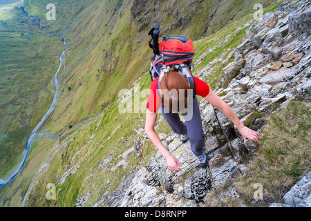 A hiker climbing Cam Crag Ridge in the Langstrath valley leading to the summit of Glaramara in the Lake District, - Stock Image