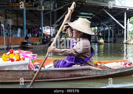Damnoen Saduak, Thailand - August 29, 2018: Woman selling garlands from a boat in Damnoen Saduak Floating Market, Ratchaburi, Thailand. - Stock Image