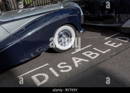 A 1964 Empress Bentley is parked in a Disabled bay in Smith Square, a small square behind the Houses of Parliament, before collecting its VIP passengers - barristers who are being sworn in as QCs (aka Silks in legal vernacular), on 11th March 2019, in London, England. - Stock Image