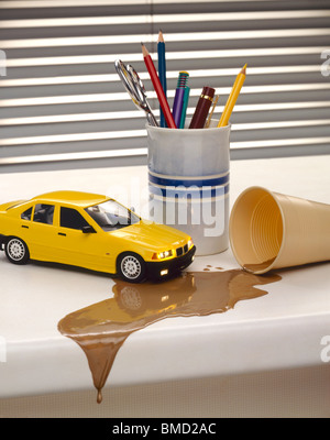 Yellow model Car on Desk with Spilt Drink - Stock Image