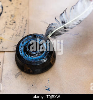 Vintage inkpot or an inkstand full of black ink and a dirty white quill on a table covered with rough brown paper - Stock Image