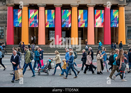 Pedestrians on Princes Street walking by the front of the Royal Scottish Academy building advertising the 2019 Summer Exhibition by Bridget Riley. - Stock Image