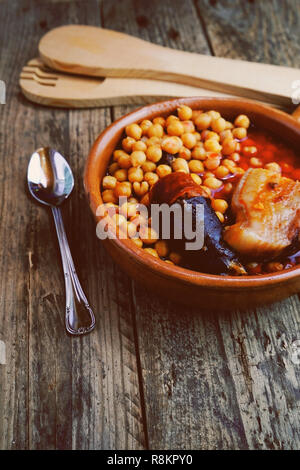Chickpeas, sausage and bacon in a crockpot by wooden spoon and fork, and a little metal spoon. Typical food from Madrid, Spain, with a rustic wooden b - Stock Image