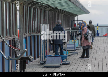 Bournemouth, Dorset, UK. 12th January 2019. Two women smile at a man walking on Boscombe Pier on a winters day. Credit: Thomas Faull/Alamy Live News - Stock Image