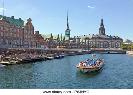 Canal cruise boat in Slotsholm Canal in Copenhagen.Christiansborg Castle, the Parliament,  the old stock exchange and dockside cafe and kayak rental. - Stock Image