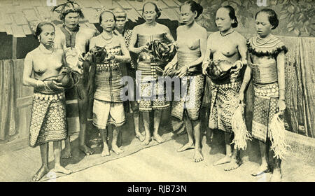 Dayak (Iban) women dancing, Borneo, SE Asia (then part of the British Empire) -- they are holding heads, trophies from their menfolk's headhunting expeditions. - Stock Image