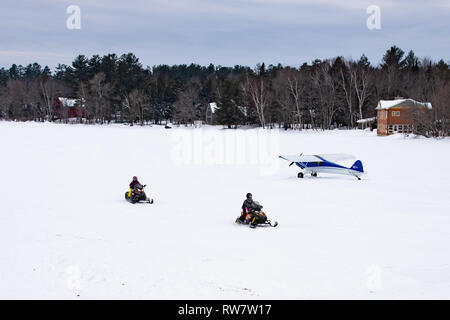 Two snowmobiles crossing Lake Pleasant in the Adirondack Mountains, NY USA past a Cub Crafters experimental aircraft on skis parked on the ice. - Stock Image