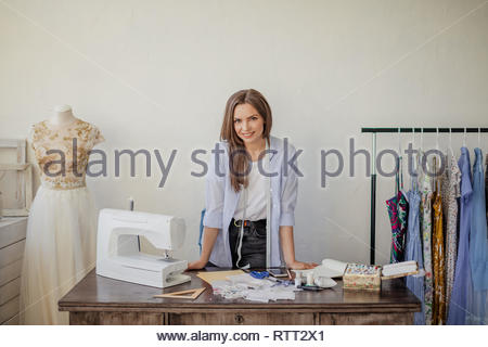 Young seamstress or dressmaker with friendly smile, looking at camera standing on her workplace in tailoring workshop. Sewing hobby, small business or - Stock Image