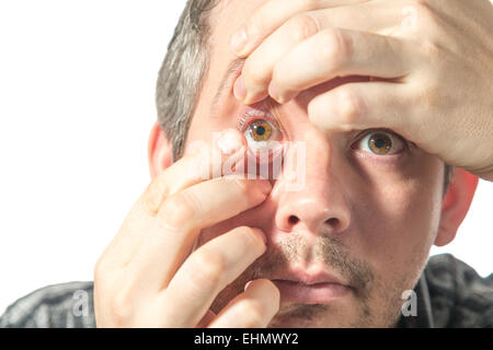 Picture of a man putting on a contact lens - Stock Image