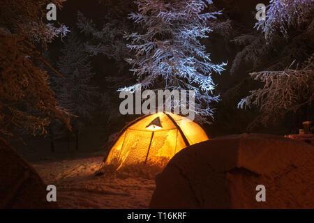Night winter camp with group of tents in snow capped forest - Stock Image