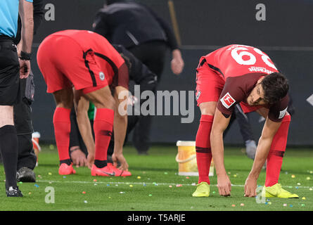 dpatop - 22 April 2019, Lower Saxony, Wolfsburg: Soccer: Bundesliga, 30th matchday: VfL Wolfsburg - Eintracht Frankfurt in the Volkswagen Arena. Interruption of the game, rubber balls (flummis) lying on the lawn, fans throwing them. Photo: Peter Steffen/dpa - IMPORTANT NOTE: In accordance with the requirements of the DFL Deutsche Fußball Liga or the DFB Deutscher Fußball-Bund, it is prohibited to use or have used photographs taken in the stadium and/or the match in the form of sequence images and/or video-like photo sequences. - Stock Image