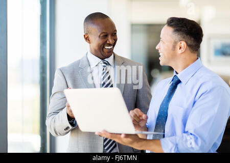 multiracial business people using laptop in modern office - Stock Image