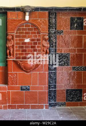 Freie Universität Thielplatz U-bahn underground railway station serves U3 line. Decorative brown & black tiled foyer. - Stock Image
