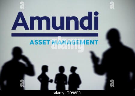 The Amundi logo is seen on an LED screen in the background while a silhouetted person uses a smartphone in the foreground (Editorial use only) - Stock Image